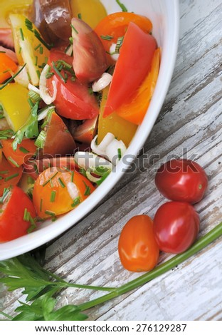tomatoes salad in plate on wooden table - stock photo