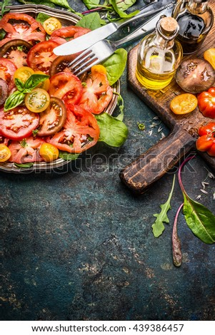 Tomatoes salad with various colorful tomatoes, olives oil and Balsamic vinegar . Plate with tomatoes salad, cutlery  and ingredients on dark rustic background, place for text, border, vertical - stock photo