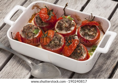 Tomatoes stuffed with herbs, spices and minced meat and baked in the oven - stock photo