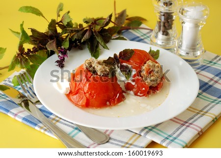 Tomatoes stuffed with meat and served with sour cream and basil. Traditional cuisine. - stock photo