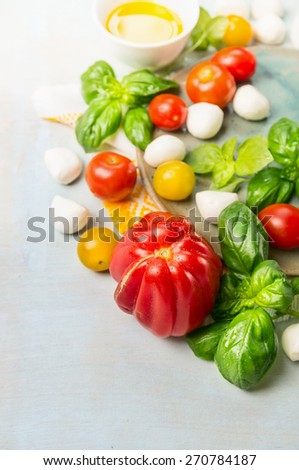 Tomatoes various with fresh basil and mozzarella on blue wooden background - stock photo