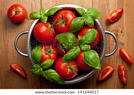 Tomatoes with basil in colander on wooden table background. Food composition. Top view - stock photo