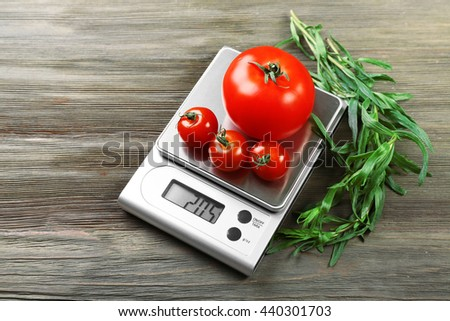 Tomatoes with digital kitchen scales on wooden background - stock photo