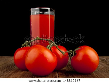 tomatoes with tomato juice on a black background - stock photo