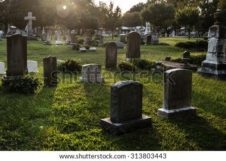 Tombstones in cemetery at dusk - stock photo