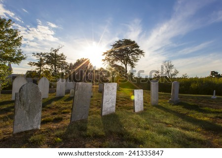 Tombstones sit quietly in an old cemetery in New England. - stock photo
