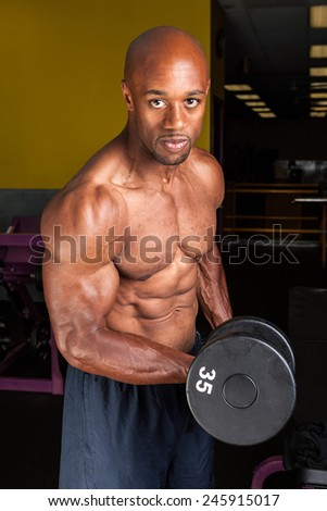 Toned and ripped lean muscle fitness man lifting weights on a curling bar - stock photo