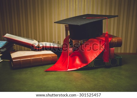 Toned closeup photo of red ribbon and graduation cap on classic table - stock photo