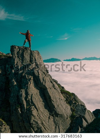 Toned image adult woman with a backpack with arms outstretched stands on the edge of a cliff and looking at the sunrise against the blue sky and thick clouds floating down - stock photo