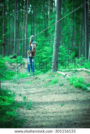 Toned image brave little boy in helmet and harness zip lining at adventure park on the background of pine trees - stock photo