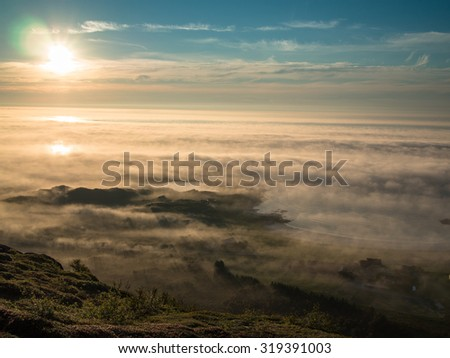 Toned image multicolored sunset above the clouds against the background of the Norwegian Sea and the countryside with road - stock photo