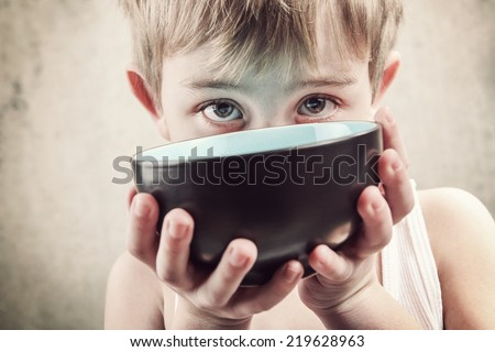 Toned image of a hungry child holding an empty bowl. - stock photo