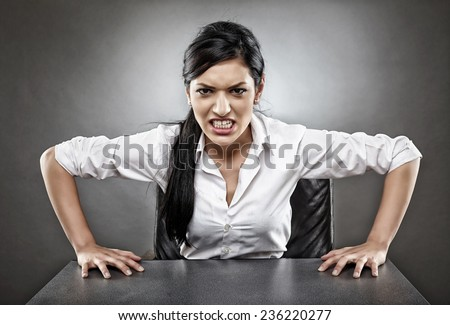 Toned image of an angry latino businesswoman bearing her teeth in rage - stock photo