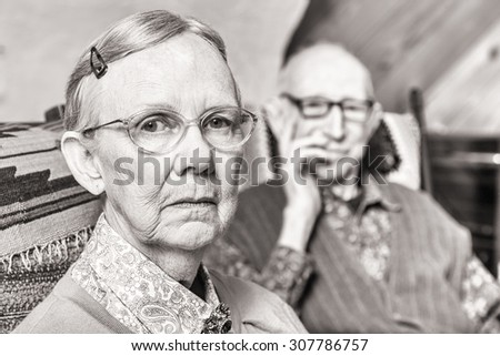 Toned image of elderly couple looking serious seated in living room - stock photo