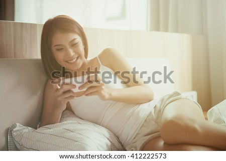 Toned image of Young smile woman playing smart phone lying on the bed at home. - stock photo