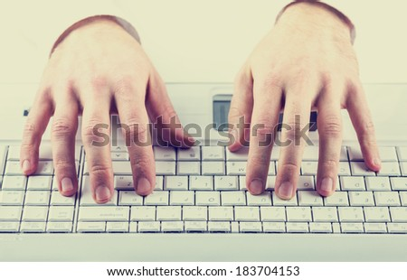 Toned instagram effect image of a man typing on a computer keyboard inputting data or information. - stock photo