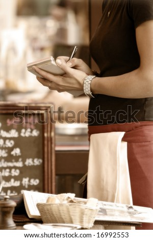Toned outdoor cafe scene with waitress taking order - stock photo