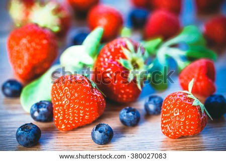 Toned photo. Color tone tuned. fresh raspberries, blueberries and strawberries on wooden background. Selective focus.  - stock photo