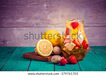 Toned photo. Color tone tuned. Strawberry lemonade with lemon in jar on wooden table. Selective focus. - stock photo