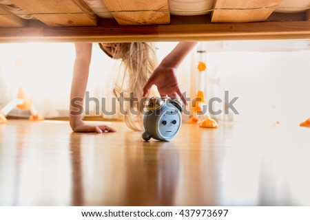 Toned photo of annoyed girl reaching for alarm clock under the bed at early morning - stock photo