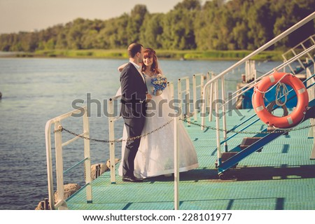 Toned photo of beautiful bride and groom standing on pier on river - stock photo