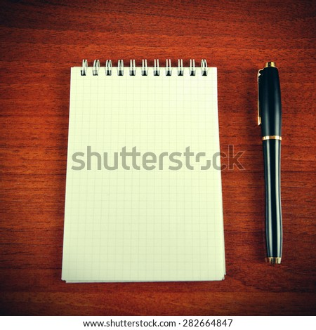Toned Photo of Blank Writing Pad and Pen on The Table - stock photo