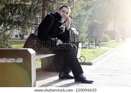 Toned photo of Cheerful Young Man with Mobile Phone at the Autumn Park - stock photo