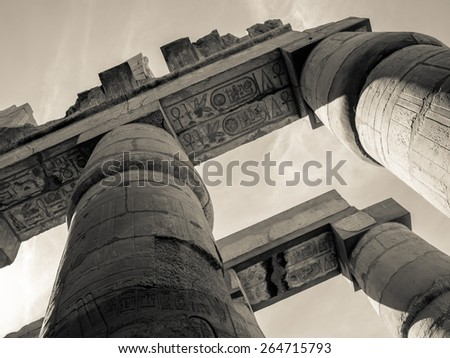 Toned photo of Egypt in retro style, sepia colors. Egyptian columns in Karnak Temple, ancient ruins in Thebes. Travel in Luxor - architecture and landmarks of ancient Egypt. - stock photo