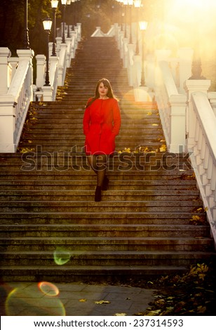 Toned photo of elegant woman walking down the stairs at park - stock photo