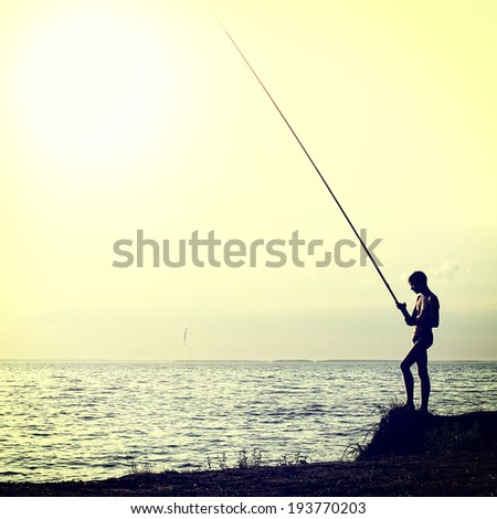Toned photo of Fisher Silhouette on Sunset background - stock photo