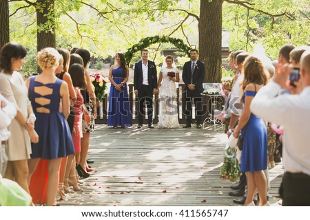 Toned photo of guests clapping to just married couple at outdoor wedding ceremony - stock photo