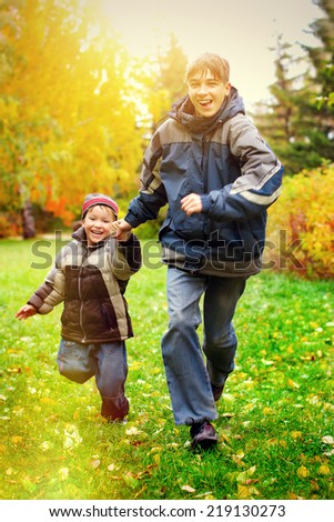 Toned photo of Happy Boys runing in the Autumn Park - stock photo