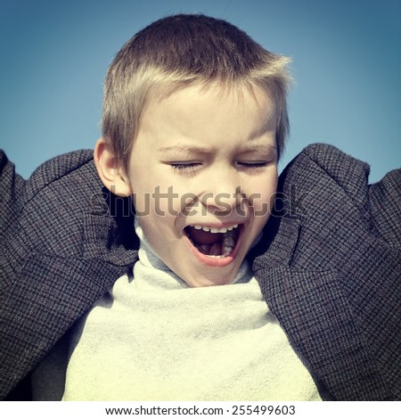 Toned Photo of Happy Kid on the blue sky background - stock photo