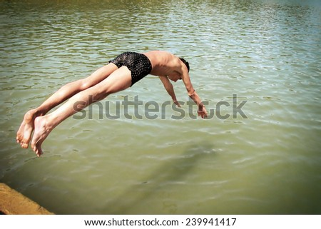 Toned Photo of happy teenager jumping in the sea - stock photo