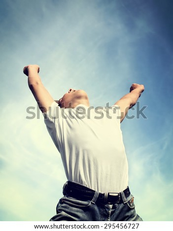 Toned Photo of Happy Young Man jump with Hands Up on the Sky Background - stock photo