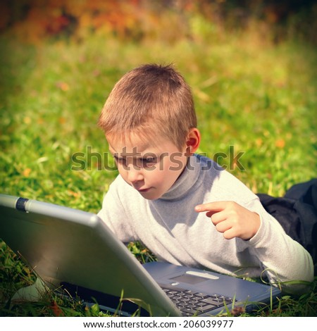Toned photo of Kid with Laptop on the Meadow - stock photo