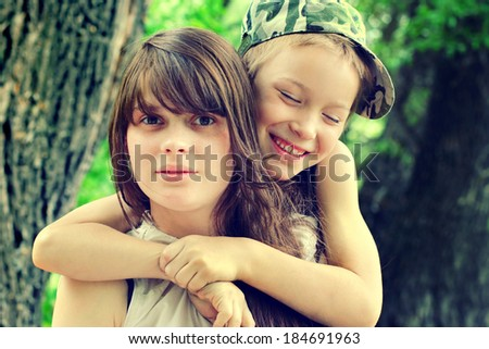 Toned photo of Little Brother and Older Sister Portrait outdoor - stock photo