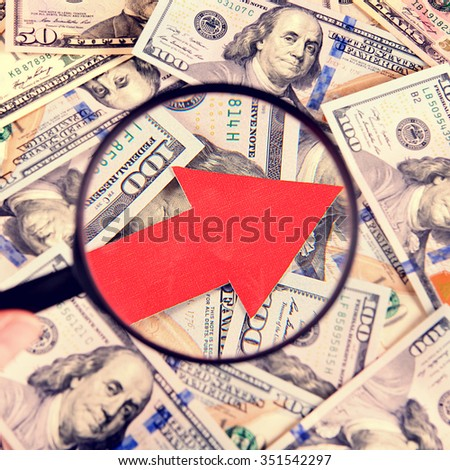 Toned Photo of Magnifying Glass on the American Dollars Background with Arrow Up - stock photo