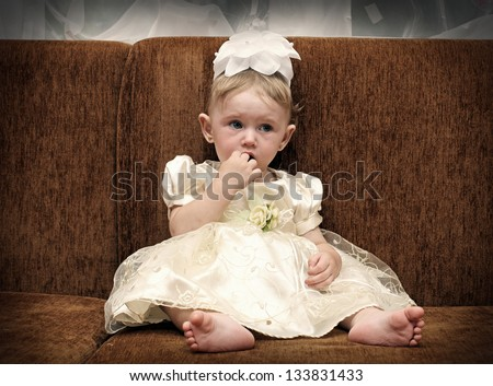 Toned Photo of Sad and Worried Little Baby on Sofa at the Home - stock photo
