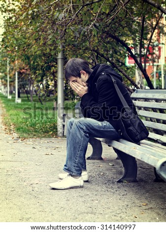 Toned Photo of Sad Young Man sit on the Bench at the City Street - stock photo