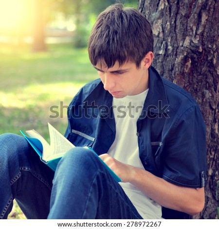 Toned Photo of Serious Teenager with the Book under the Tree - stock photo