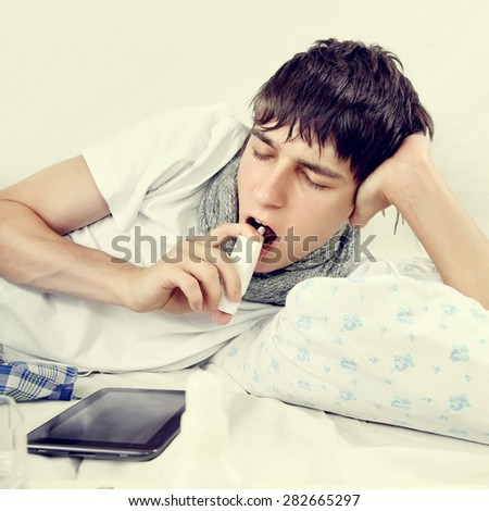 Toned Photo of Sick Young Man using Inhaler on the Bed - stock photo