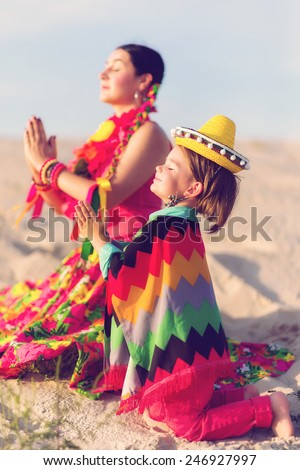 Toned photo of son and mother dressed in Mexican clothes praying together - stock photo
