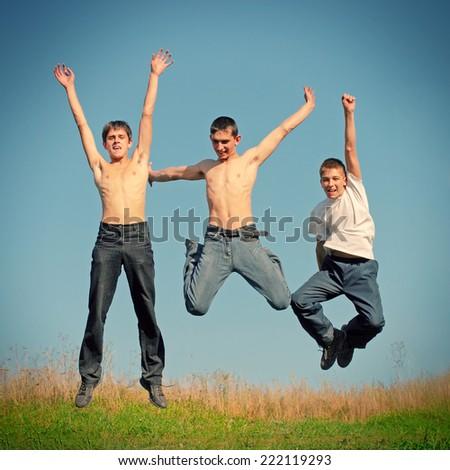 Toned photo of Three Happy Tennage Boys jumping - stock photo