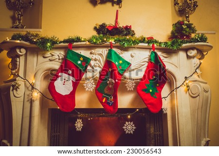 Toned photo of three red Christmas socks hanging on fireplace at house - stock photo