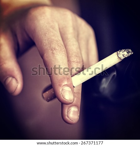 Toned Photo of Ugly Hand with Cigarette closeup - stock photo