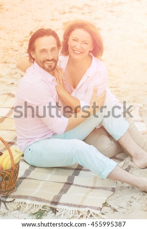 Toned picture of beautiful middle-aged couple kissing and enjoying their evening. Beautiful lady and handsome man resting at beach during sunset. - stock photo