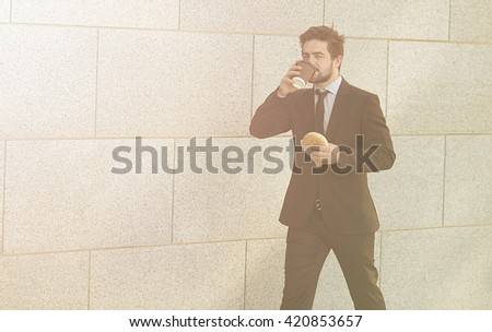 Toned picture of businessman eating junk food and speaking over mobileor smart phone while walking along street to office. - stock photo