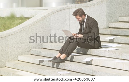 Toned picture of businessman in black business suit using laptop computer while sitting n city center. Freelance concept. - stock photo