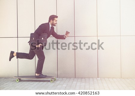 Toned picture of businessman on longboard and with cup of coffee going to office. Freelance man in black business suit hurrying. - stock photo